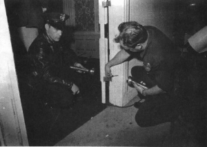 LAPD officers Rozzi and Wright inspect a bullet hole discovered in a door frame in a kitchen corridor of the Ambassador Hotel in Los Angeles near where Robert F. Kennedy was shot. A bullet is still in the wood. (California State Archives)