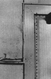 FBI photograph - View taken inside the kitchen serving area showing doorway leading into the kitchen from the staging area. The lower right corner of the photograph shows two bullet holes, which are circled. The missing portion of the panel also reportedly contained a bullet. (California State Archives)