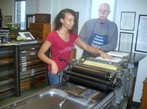 Dr. Michael Peich watches over Valerie Reason as she prints her poems. (Candice Monhollan)