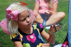 A young girl feeds a butterfly at the annual festival in Royersford. (Candice Monhollan)
