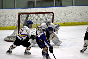 Downingtown East's Justin Cohn attempts to redirect a shot by Downingtown West goaltender John Kelly in a 4-1 win Wednesday night. (Candice Monhollan)