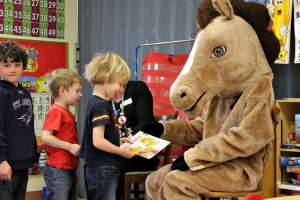 Laura Harbago and Chester the Horse read a Berenstain Bears book to Lisa Gerber's Pre-K class at St. Agnes School after winning the Chester County Health Department's Immunization Coloring Contest on April 20. (Candice Monhollan)