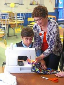 Joanne Dearlove, right, instructs Chris Titchenell how to sew a pillowcase at St. Agnes School in West Chester on Wednesday. (Vinny Tennis)
