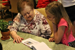 "Heather Lamb, right, reads the biography of her ""buddy"" Mary Crepeau, left, at Sunrise Assisted Living as part of the Living History project May 13. (Candice Monhollan)"