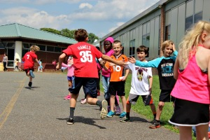 Kindergarten children high-five fifth graders as they take their turn running and walking as part of Kids for the Cure at Fern Hill Elementary on May 22. (Candice Monhollan)