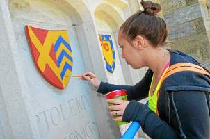 Michelle McEvoy paints a crest over the archway of Philips Hall on the campus of West Chester University in West Chester on Thursday, May 14, 2015. (Vinny Tennis)