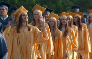 A graduate waves to family members in the stands during the processional at the commencement exercises at Bayard Rustin High School in West Chester on Tuesday, June 9, 2015. (Vinny Tennis)