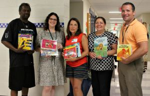 From left, Bernard Harris, Jr., Melissa Kleiman, Angie Scherffel, Carol Baker and P.J. Dakes helped pass out bundles of books to children at Westtown-Thornbury Elementary School on Wednesday. (Candice Monhollan)