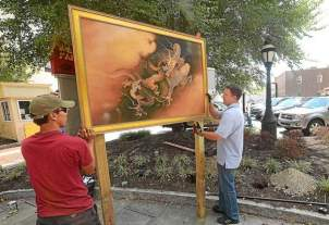 P.J. Jantaev and Ivan Gertsen of H & G Sign Company raise a reproduction of 'Two Dragons (in clouds)' by Kano Hogai on E. Gay Street at the Wells Fargo Parking lot. The work is part of The Philadelphia Museum of Art and the West Chester Park & Recreation Department exhibiting replica art throughout the borough as part of Inside/Out. The work began to go up on Thursday. (Pete Bannan)