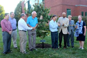 "Members of the county and West Goshen took part in the unveiling of the white dogwood tree and plaque planted in front of the West Goshen Township building in honor of the late Robert ""Doc"" White a year after his death. His son, Doug (fourth from the right), cut the ribbon during the ceremony. (Candice Monhollan)"