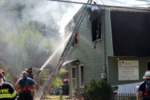 Firefighters attempt to put out a fire in a house by the corner of Hopewell Road and Route 322 in East Brandywine Township on Monday. The one-alarm fire spread on both floors of the home. (Candice Monhollan)