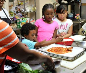 Chris Oliveras, left, spreads on homemade tomato sauce onto his healthy pizza as part of the Melton Center's new cooking and nutrition classes. (Candice Monhollan)