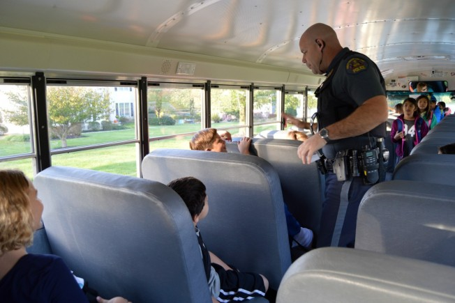 Detective Jeffrey McCloskey of the West Whiteland Police Department rode the bus to Exton Elementary School to talk to the students about school bus safety as part of Operation Safe Stop on Wednesday morning. Officers were also present at the bus stop at Route 100 and Rockland Drive to cite people driving past a stopped bus. (Tracey Dukert)
