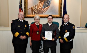 "Daniel ""DJ"" Matthews, a volunteer firefighter and senior at West Chester University, was honored by the borough for rescuing four people from a burning building in March. Pictured here from left are West Chester Fire Chief Mike McDonald, Mayor Carolyn Comitta, Matthews and West Chester Assistant Fire Chief Steve Pelna. (Nancy Gainer)"