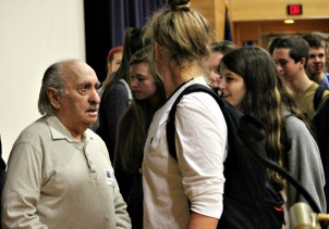 West Chester Rustin High School students meet with Holocaust survivor David Tuck to shake his hand and take pictures with him on Monday morning. (Candice Monhollan)