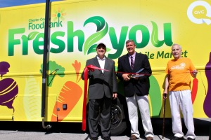 The Chester County Food Bank celebrates with a ribbon cutting for the Fresh2You Mobile Market as it enters its second year. From left, state Sen. Andy Dinniman, D-19, of West Whiteland; Larry Welsch, executive director of the food bank; and Elmer Duckinfield, an original founder of the Chester County Gleaning Program. (Candice Monhollan)