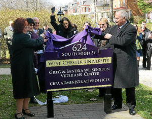 Retiring West Chester University President Greg Weisenstein and his wife, Sandra, unveil the new sign for the Greg & Sandra Weisenstein Veterans Center on High Street. (Pete Bannan)