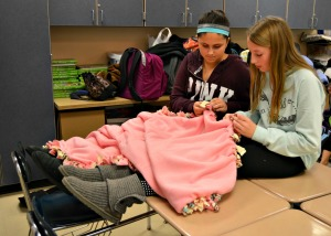 Volunteers from Fugett Middle School make 65 fleece blankets for the nonprofit Cozies 4 Chemo Monday afternoon. (Tracey Dukert)