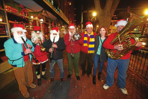 The Santa Band was out on the streets of West Chester Dec. 18, 2014, raising money for the homeless of Chester County. From left are Bob Fanelli; David Flaherty; Phil Forlano; Bob Carl; Glenn Fricke, executive director of Safe Harbor; Karen Manzone, volunteer coordinator of Safe Harbor; and Mike Byrne. (Pete Bannan)