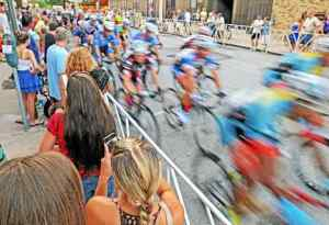 In this file photo, racers blur by spectators on North Church Street during the Iron Hill Twilight Criterium, which was held July 6, 2013, in downtown West Chester. (Daily Local News)